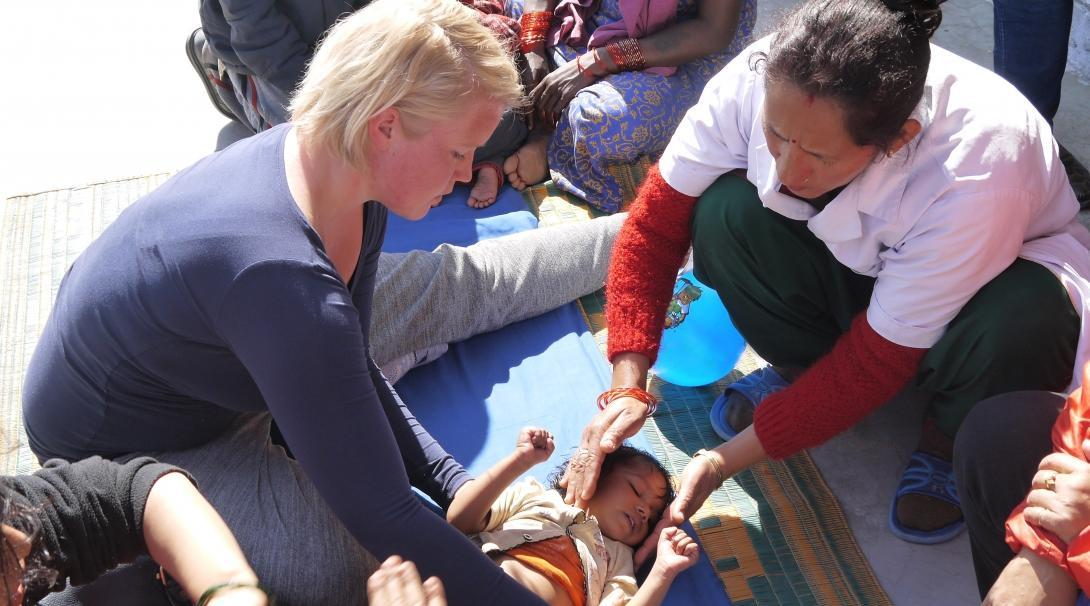 Female Projects Abroad intern is pictured helping a discomforted child during her physiotherapy internship in Nepal.